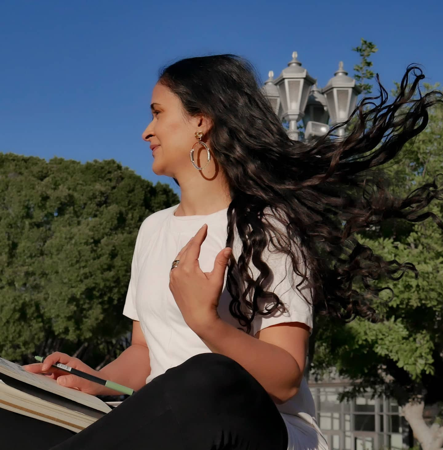photo of Ludy (ludmila) sitting against trees and street lamps flipping her hair